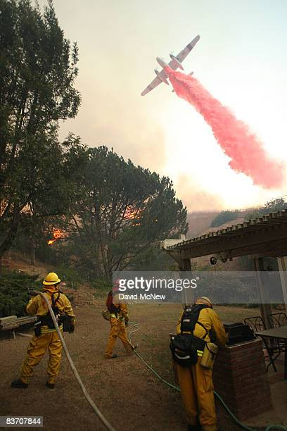 A firefighting airtanker drops PhosCheck fire retardant over firefighters trying to protect a house from the Corona Fire on November 15 2008 in Yorba...