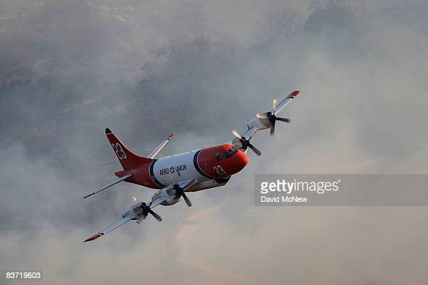 DC10 firefighting airtanker flies from a smokefilled canyon after dropping fire retardant on the northern flank of a wildfire threatening thousands...
