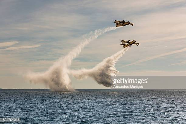 Firefighting amphibious aircrafts releasing water at sea