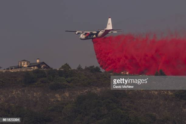 Firefighting Coulson C-130 air tanker drops fire retardant near a house during the Oakmont Fire on October 15, 2017 near Santa Rosa, California. At...