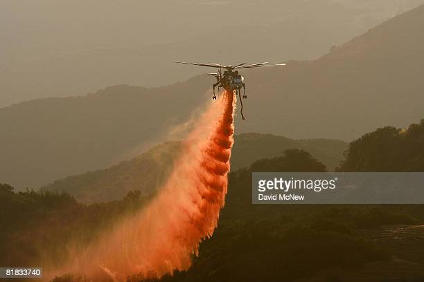 A firefighting Erickson AirCrane helicopter drops PhosCheck fire retardant on the northern front of the Gap fire as more than 1000 wildfires continue...