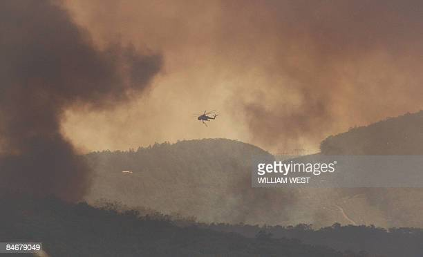 A firefighting helicopter approaches an out of control fire in the Bunyip State Park near Labertouche some 125 kilometres west of Melbourne on...