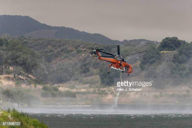 A firefighting helicopter draws water from Lake Cachuma while fighting the Whittier Fire in the Los Padres National Forest near Lake Cachuma Santa...