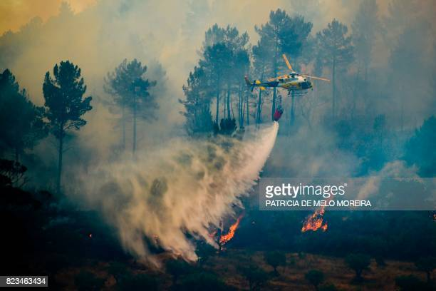 TOPSHOT A firefighting helicopter drops it's load over a wildfire near Vila Velha de Rodao central Portugal on July 27 2017 Forest fires raged in the...