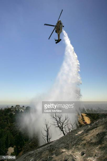 Firefighting helicopter drops water near Griffith Observatory to create a fireline on the western flank of a wildfire in Griffith Park, the nation's...