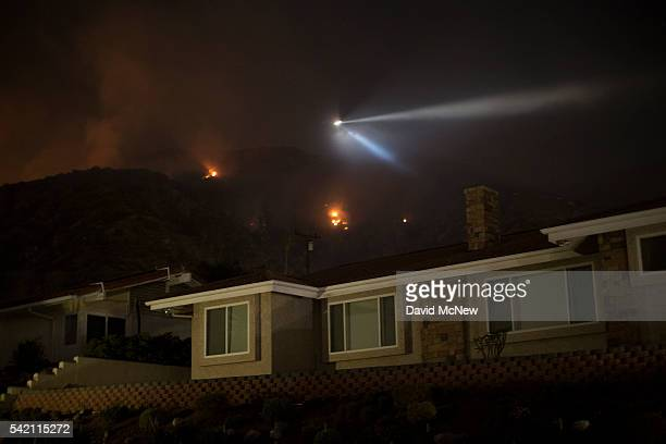 A firefighting helicopter drops water near some 700 evacuated homes to protect against an expected wind shift at the San Gabriel Complex Fire in the...
