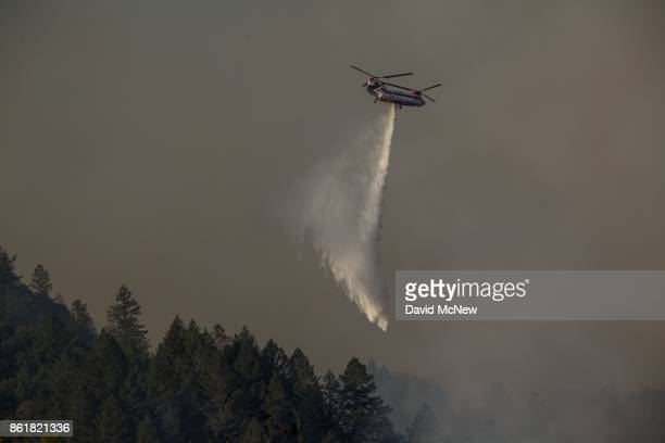 A firefighting helicopter drops water on the Tubbs Fire on October 15 2017 near Santa Rosa California At least 40 people were killed with many are...