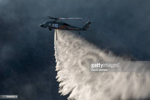 A firefighting helicopter drops water over the Getty Fire on October 28 2019 in Los Angeles California Reported at 130 am the fire burned several...