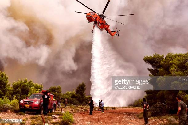 A firefighting helicopter drops water to extinguish flames during a wildfire at the village of Kineta near Athens on July 24 2018 Raging wildfires...