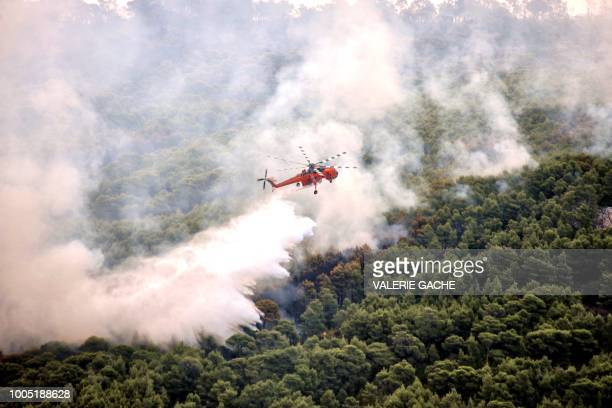 TOPSHOT A firefighting helicopter drops water to extinguish flames during a wildfire at the village of Kineta near Athens on July 25 2018 At least 79...