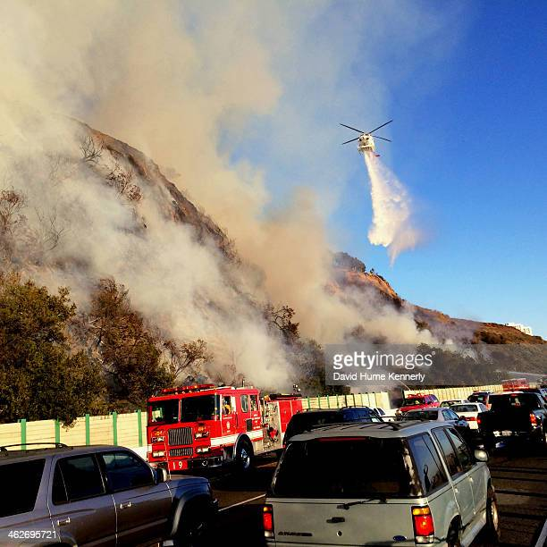 A firefighting helicopter dumps water on a brush fire alongside the Pacific Coast Highway January 14 2014 in Santa Monica California More than 160...