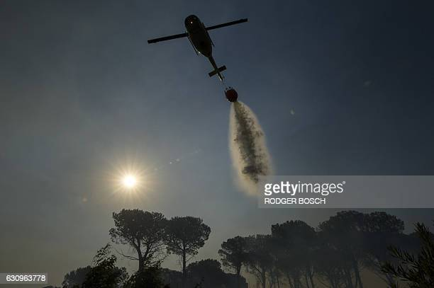 TOPSHOT A firefighting helicopter dumps water on a vegetation fire that has been burning in the mountains for the last two days above the town of...