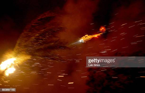 A firefighting helicopter flies over a burning palm tree as it prepares to make a water drop on the Canyon Fire on September 25 2017 in Corona...