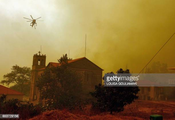 A firefighting helicopter flies over a church in the burning village of Platanos 26 August 2007 The death toll from Greece's fires rose to 57...