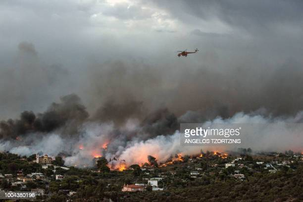 A firefighting helicopter flies over a wildfire raging in the town of Rafina near Athens on July 23 2018 At least five people have died and more than...