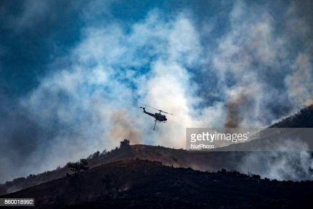 A firefighting helicopter flies over charred hills engulfed in smoke in Anaheim California on October 10 2017 14 helicopters 6 airplanes and over...