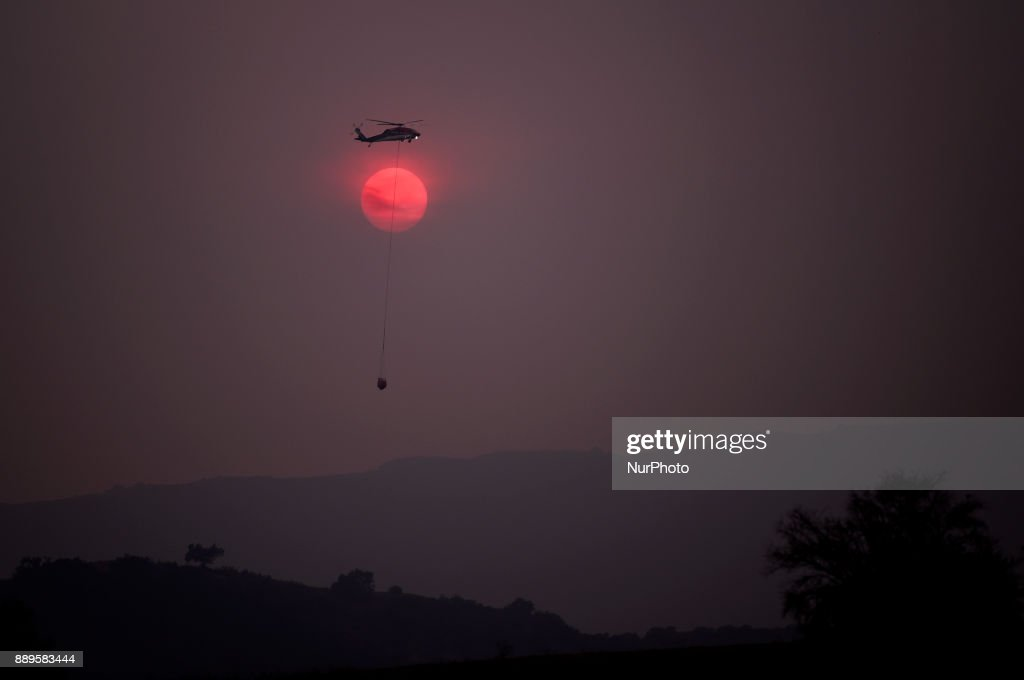 A firefighting helicopter flies over the Thomas wildfire as the sun sets in Ojai, California on December 9, 2017. The wind-fueled fire burned through an area of 240 square miles, destroyed hundreds of homes and prompted massive mandatory evacuations.