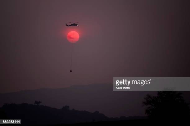 Firefighting helicopter flies over the Thomas wildfire as the sun sets in Ojai, California on December 9, 2017. The wind-fueled fire burned through...