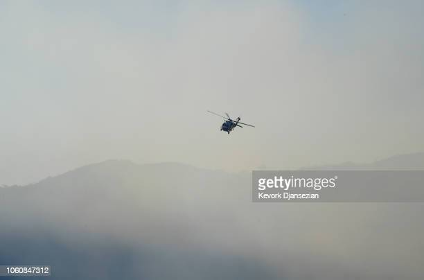 A firefighting helicopter flies through the smoke as it continues to put out hotspots on November 12 2018 in Calabasas California as the Woolsey Fire...