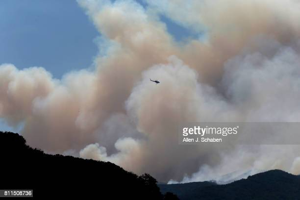 A firefighting helicopter gets into position to make a water drop on the Whittier Fire as it burns towards SR154 in the Los Padres National Forest...