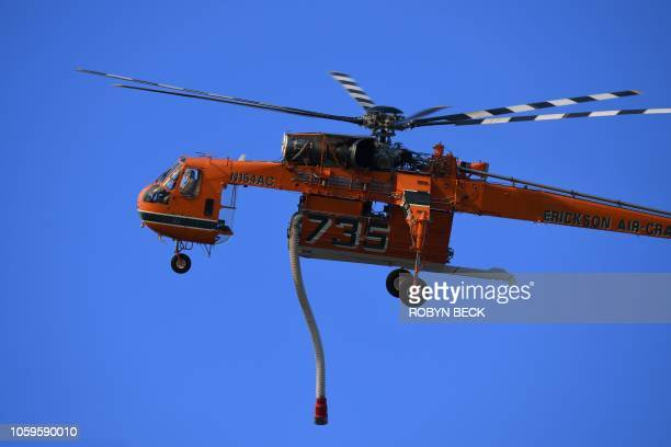 A firefighting helicopter heads to the area near the Los Angeles Zoo in Griffith Park in Los Angeles California November 9 2018 as a wildfire burns...