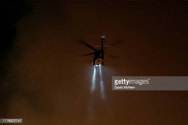 A firefighting helicopter hovers over the Maria Fire which exploded to 8000 acres on its first night on November 1 2019 near Somis California...
