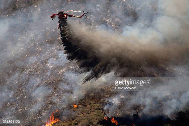 A firefighting helicopter makes a drop as firefighters try to gain control of the fire above homes along Cajon Boulevard at the Blue Cut Fire on...