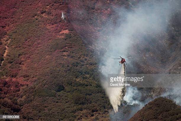A firefighting helicopter makes a drop near a hillside painted red with fire retardant as firefighters work to protect homes along Cajon Boulevard at...