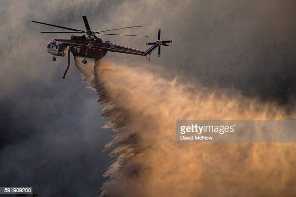 A firefighting helicopter makes a drop near Cajon Boulevard at the Blue Cut Fire on August 18 2016 near Wrightwood California An unknown number of...