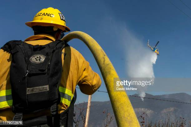 A firefighting helicopter makes a water drop near firefighters battling the Easy Fire on October 30 2019 near Simi Valley California The National...