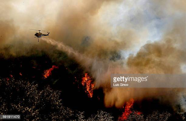 A firefighting helicopter makes a water drop on a flareup of the Blue Cut fire along Interstate 15 in the Cajon Pass on Thursday Aug 18 2016
