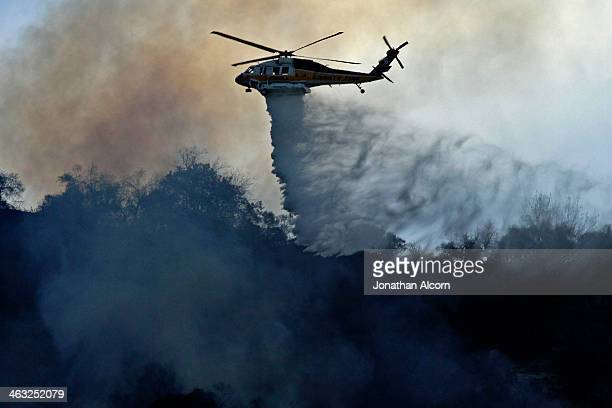 A firefighting helicopter makes a water drop on the Colby Fire burning for a second day in the hillside above Highway 39 in Azusa California Three...