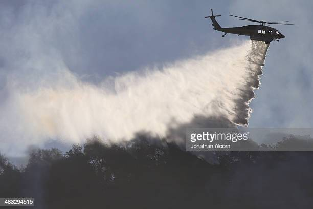 A firefighting helicopter makes a water drop on the Colby Fire burning for a second day in the hillside above Highway 39 on January 17 2014 in Azusa...