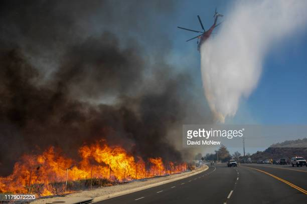 Firefighting helicopter makes a water drop over the Easy Fire on October 30, 2019 near Simi Valley, California. The National Weather Service issued a...
