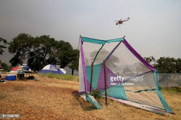 A firefighting helicopter passes by as tents food and personal belongs remain abandoned after campers were evacuated from the fastmoving Whittier...