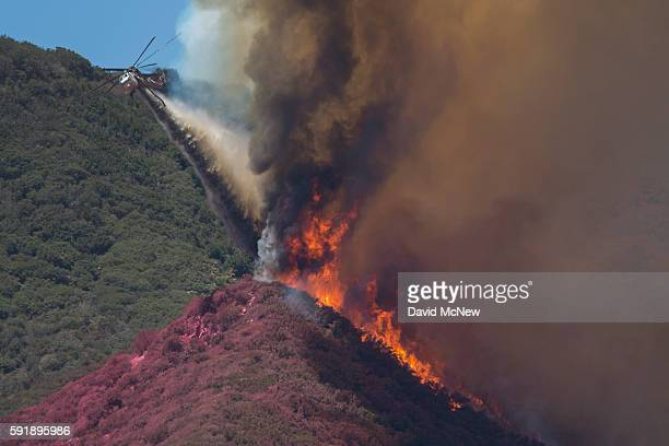 A firefighting helicopter pilot tries to stop flames close to jumping a ridge even though the ridge is already painted red with fire retardant above...
