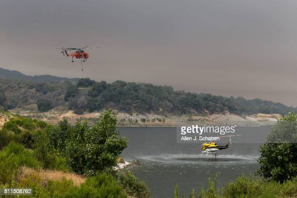 Firefighting helicopters draw water from Lake Cachuma while fighting the Whittier Fire in the Los Padres National Forest near Lake Cachuma Santa...