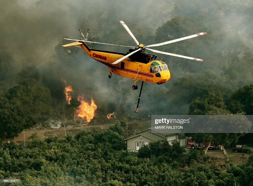 Firefighting helicopters try to save a house from the Thomas wildfire in Carpinteria, California on December 10, 2017. The Thomas fire is only 15 percent contained, now threatening the city of Santa Barbara and the nearby coastal town of Carpinteria, making it one of the worst wildfires in California history. RALSTON