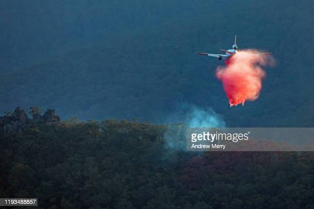 firefighting jet aircraft flying low in mountain valley at dusk, blue mountains, australia - bushfire australia stock pictures, royalty-free photos & images
