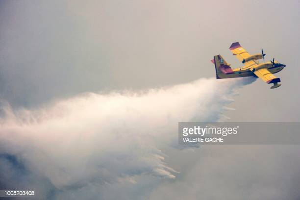 A firefighting plane empties the water over the flame during a wildfire at the village of Kineta near Athens on July 25 2018 At least 79 people died...