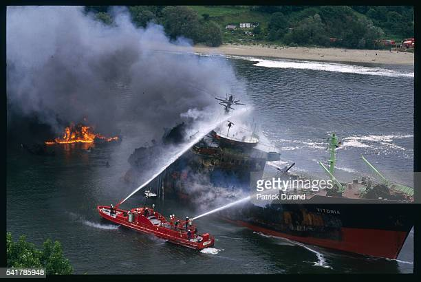 Firefighting ships extinguish the flames from a collision between two petrol tankers on the river Seine in Aizier in the Eure The tankers came from...