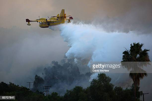 A firefighting Super Scooper airtanker drops water over the Brea Fire on November 15 2008 near Yorba Linda California Strong Santa Ana Winds are...
