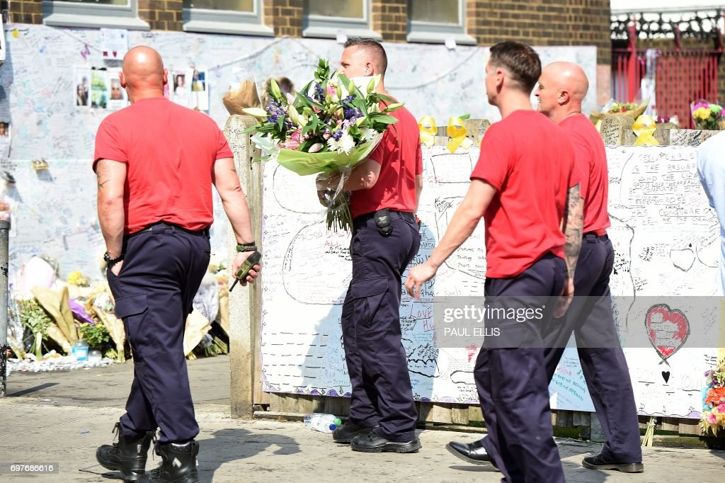 Firefights arrive to leave tributes to the victims of the Grenfell Tower fire, a residential tower block in Kensington, west London, on June 19, following the June 14 fire which gutted the residential building. Seventy-nine people are dead or missing and presumed dead following a devastating blaze in a London tower block, police said Monday, as Britain held a minute's silence for the victims. /