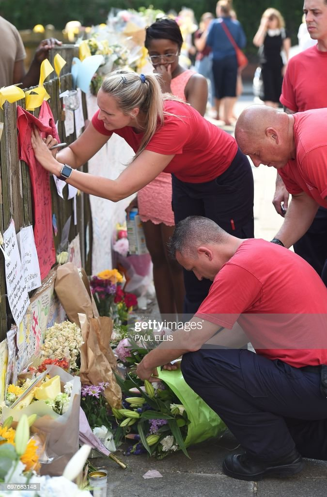 Firefights leave tributes to the victims of the Grenfell Tower fire, a residential tower block in Kensington, west London, on June 19, following the June 14 fire which gutted the residential building. Seventy-nine people are dead or missing and presumed dead following a devastating blaze in a London tower block, police said Monday, as Britain held a minute's silence for the victims. /
