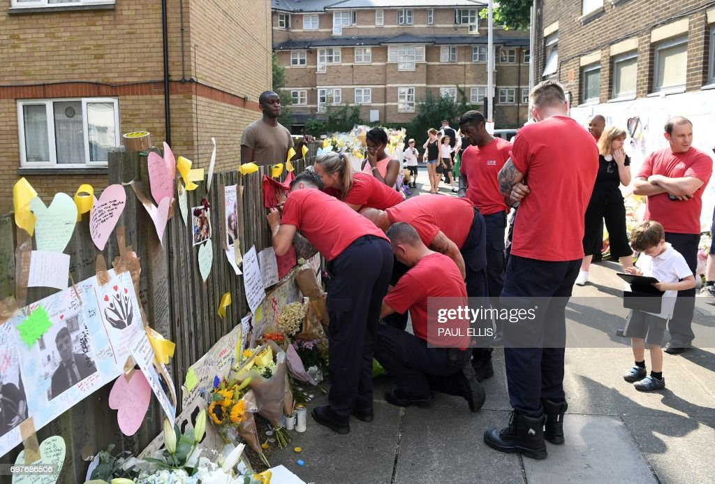 Firefights leave tributes to the victims of the Grenfell Tower fire, a residential tower block in Kensington, west London, on June 19, following the June 14 fire which gutted the residential building. Seventy-nine people are dead or missing and presumed dead following a devastating blaze in a London tower block, police said Monday, as Britain held a minute's silence for the victims. / AFP PHOTO / Paul ELLIS