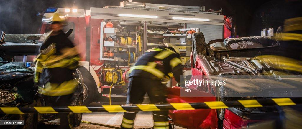 Firefigters en una escena del accidente de coche : Foto de stock