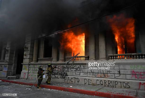 Firefigthers try to extinguish a fire at the Congress building during a protest demanding the resignation of Guatemalan President Alejandro...