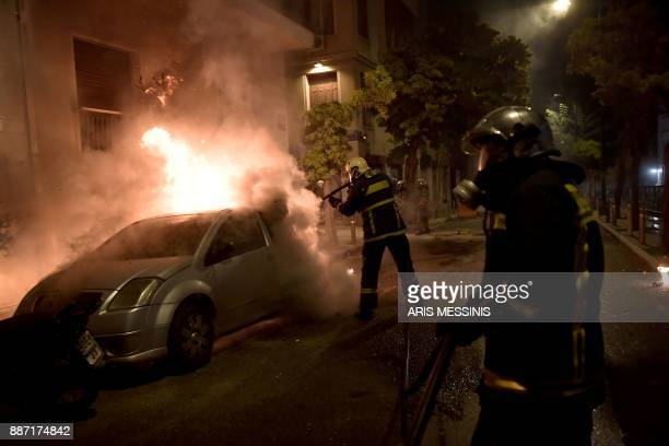 Firefiters extinguish a burning car during clashes between protesters and riot police in central Athens on December 6 after a demonstration...