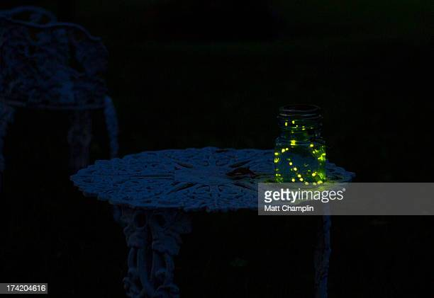 Fireflies at night in a glass jar