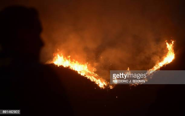 A firefughter watches as fire erupts across a Romero Canyon hillside in Montecito California north of Santa Barbara on December 12 2017 Crews...